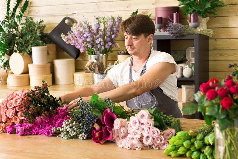 Man assistant in flower shop delivery make rose bouquet royalty free stock images