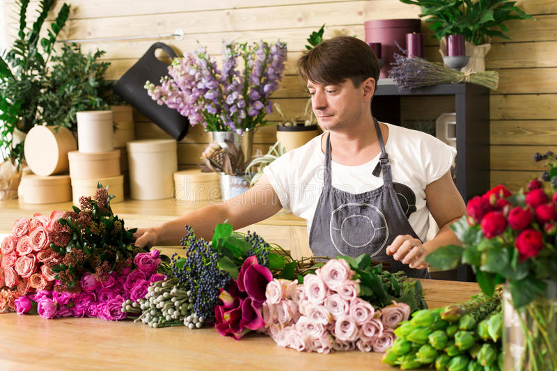 Man assistant in flower shop delivery make rose bouquet stock photos