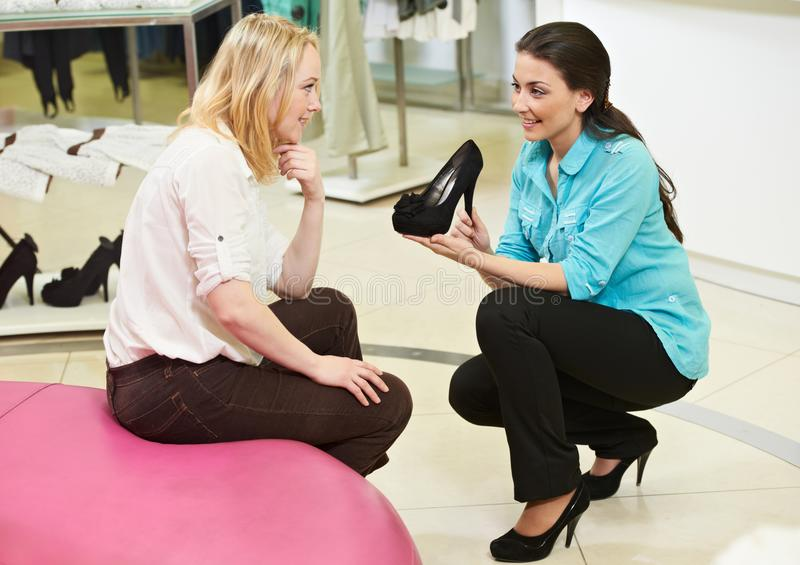 Man and assistant at shoe shopping stock image