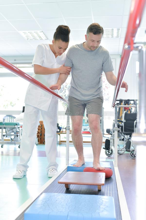 Man assisted by nurse in rehab clinic royalty free stock images