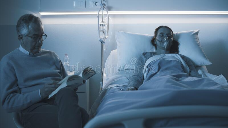 Man assisting her young daughter at the hospital stock image