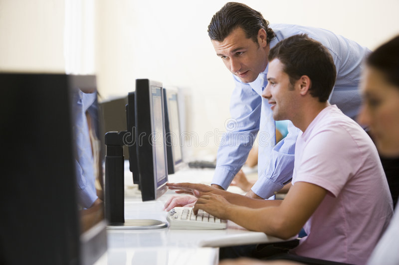 Man assisting other man in computer room stock images