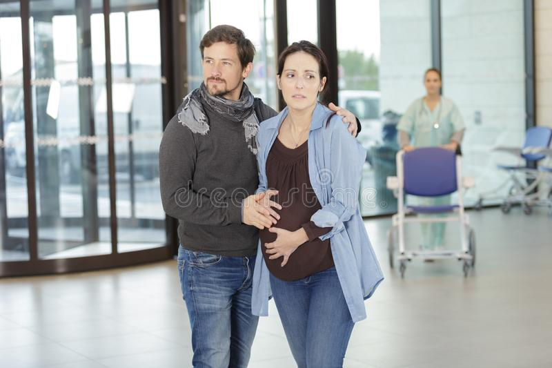 Man assisting woman to labor room royalty free stock photos