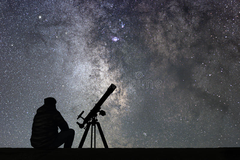 Man with astronomy telescope looking at the stars. Man telescope and starry sky. Night sky. Milky way galaxy royalty free stock photography