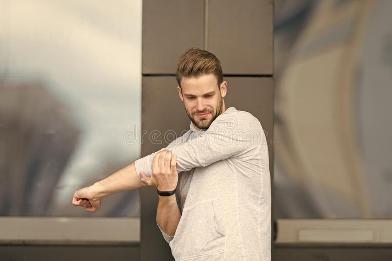 Man athlete concentrated face stretching arms before workout, urban background. Runner stretching training outdoor. Sportsman prepare muscles and joints for royalty free stock photography