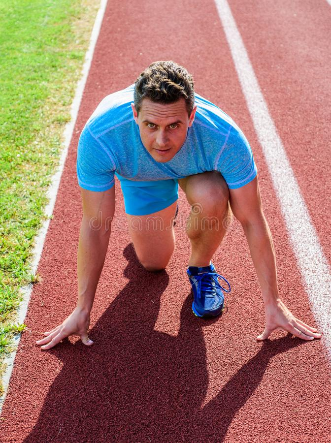 Man athlete focused on running race ready to go. Runner athlete concentrated low start position. Runner take part. Competitions low start position. Focused on royalty free stock photography
