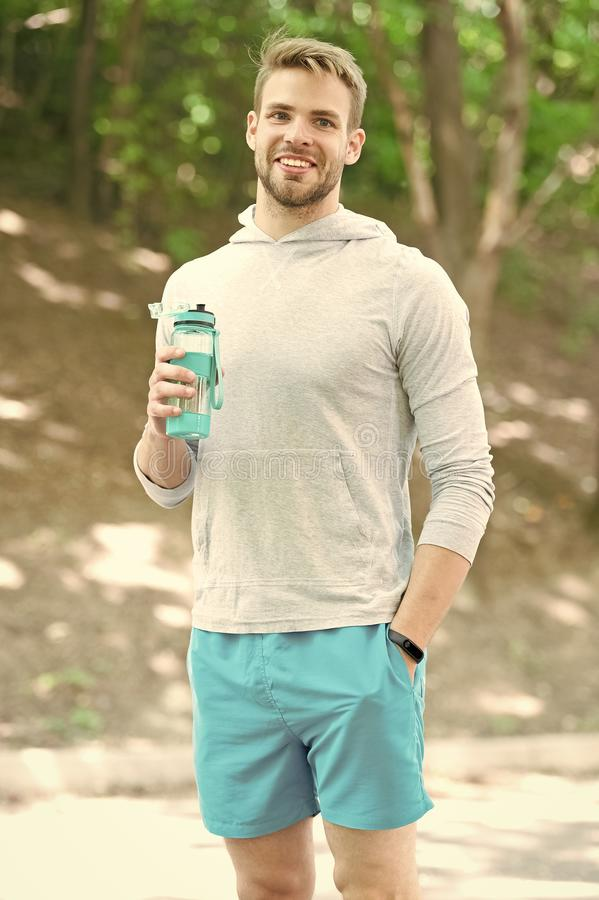 Man athlete hold bottle care hydration body after workout. Refreshing vitamin drink after great workout. Man athletic. Appearance holds water bottle. Athlete stock photos