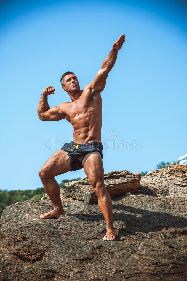 Man Athlete on a rock by the sea royalty free stock photos