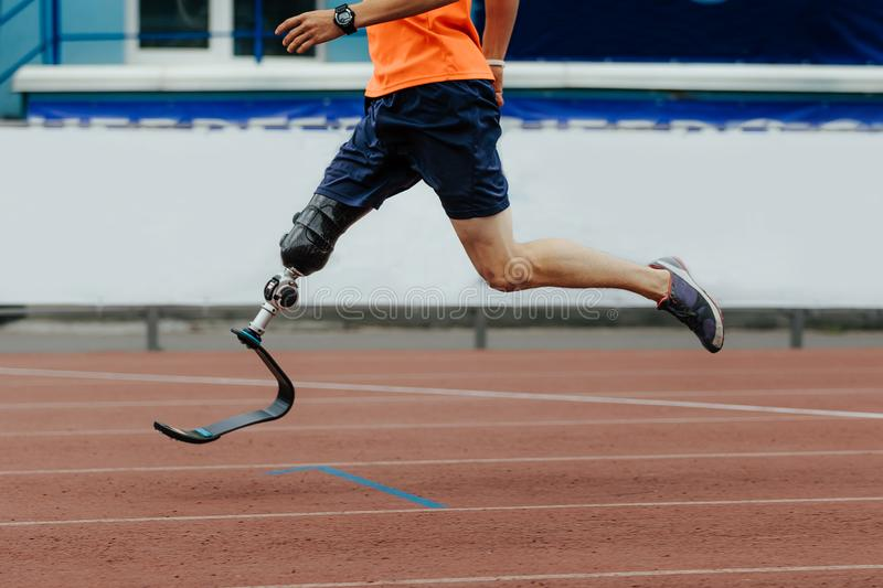 Man athlete runner artificial leg limb. Running in stadium stock image