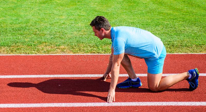 Man athlete runner stand low start position stadium path sunny day. Make effort for victory. Runner ready to go. Adult. Runner prepare race at stadium. How to stock photo