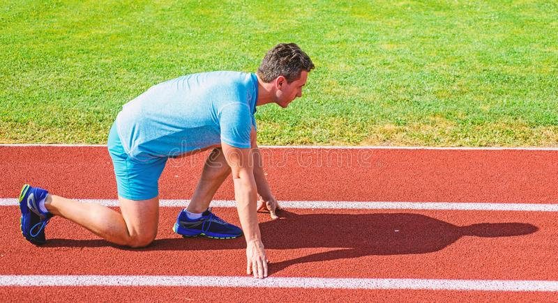 Man athlete runner stand low start position stadium path sunny day. Make effort for victory. Runner ready to go. Adult. Runner prepare race at stadium. How to royalty free stock photo