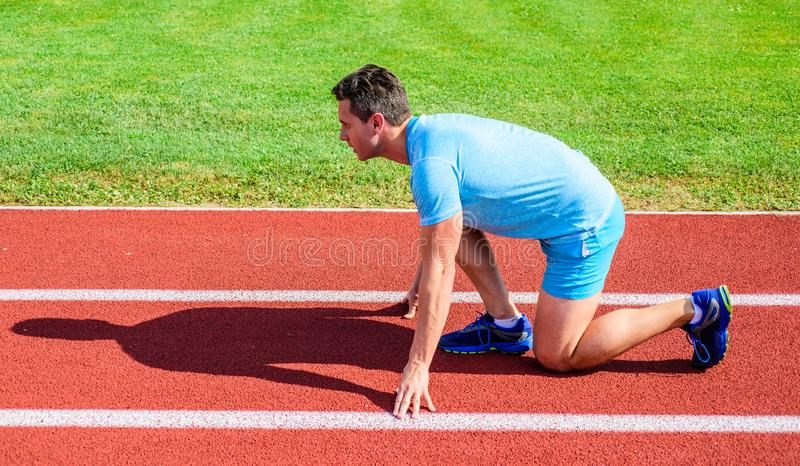 Man athlete runner stand low start position stadium path sunny day. Runner ready to go. Make effort for victory. Sport. Motivation concept. Adult runner prepare royalty free stock image