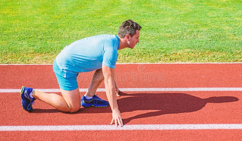 Man athlete runner stand low start position stadium path sunny day. Runner ready to go. Make effort for victory. Sport. Motivation concept. Adult runner prepare stock image