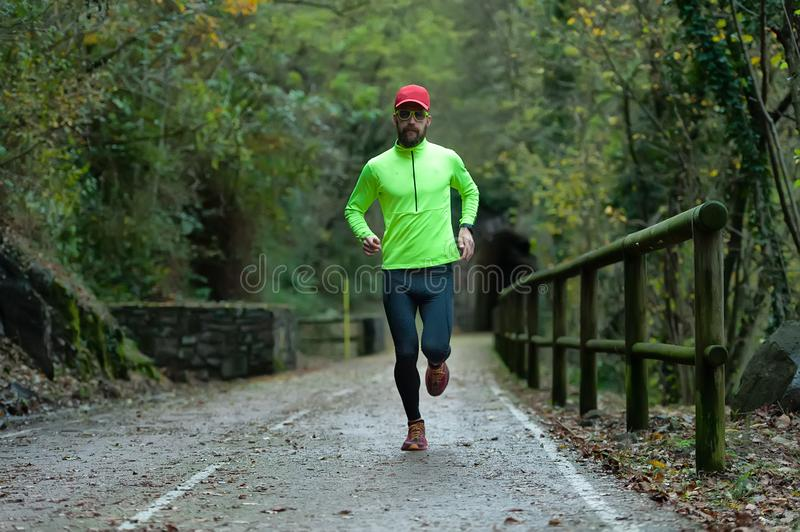 Man athlete runs on bicycle lane in the fall stock images