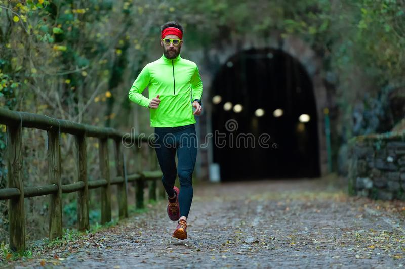 Man athlete runs on bike path between tunnels in the fall stock photo