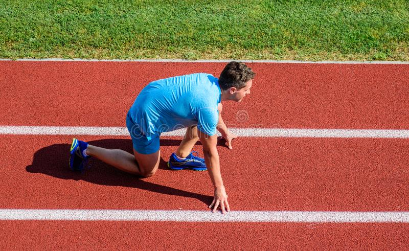 Man athlete stand low start position at stadium path. Beginning of new lifestyle habit. Runner ready to go. Athlete. Runner prepare to race at stadium. How to royalty free stock photography
