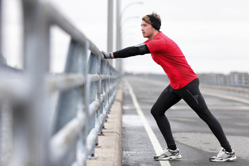 Man athlete stretching legs in winter outdoor run royalty free stock photo