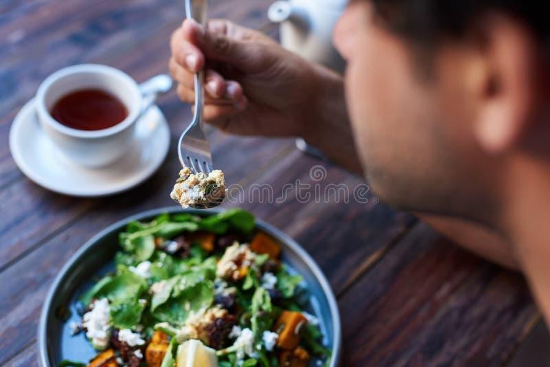 Man att äta läcker sallad, medan sitta på en bistrotabell royaltyfria bilder