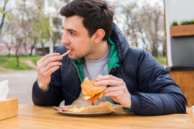 Man att äta stekte potatisar med en hamburgare i gatamatkafé fotografering för bildbyråer