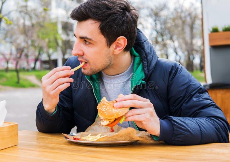 Man att äta stekte potatisar med en hamburgare i gatamatkafé royaltyfria foton