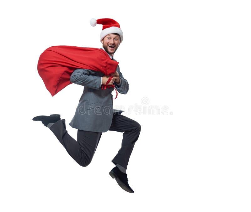 Man att bära som Santa Claus som hoppar den röda påsen över skuldra arkivbild
