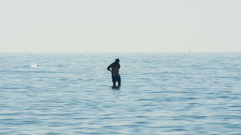 Man att beskåda som omges av vatten, kontur av en man i mitt av havet arkivfoton