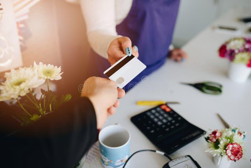 Man att betala för blommor med hans debiteringkort royaltyfri fotografi