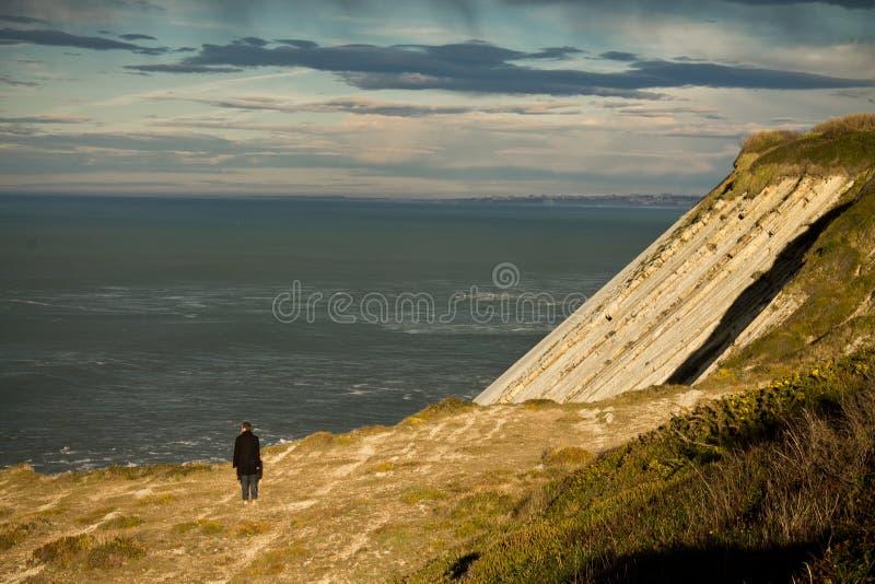 Man att beundra den atlantiska kustavsatsklippan vid havet i underbart himmelsolljus i det basque landet, Frankrike arkivbild