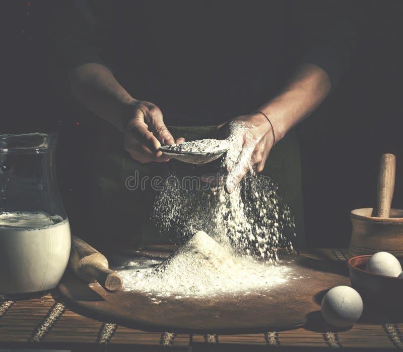 Man att förbereda upp bröddeg på trätabellen i ett bagerislut Förberedelse av påskbröd royaltyfria bilder