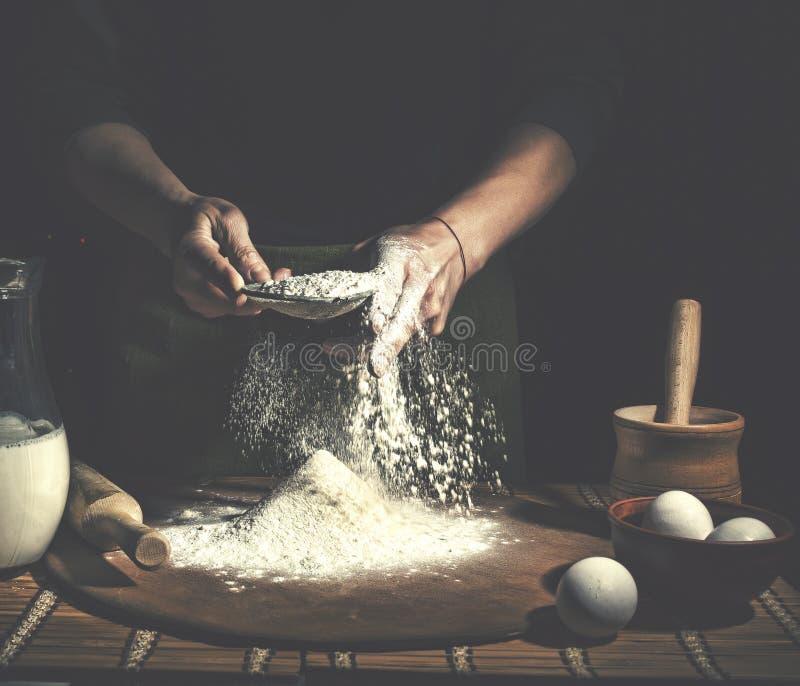Man att förbereda upp bröddeg på trätabellen i ett bagerislut Förberedelse av påskbröd fotografering för bildbyråer