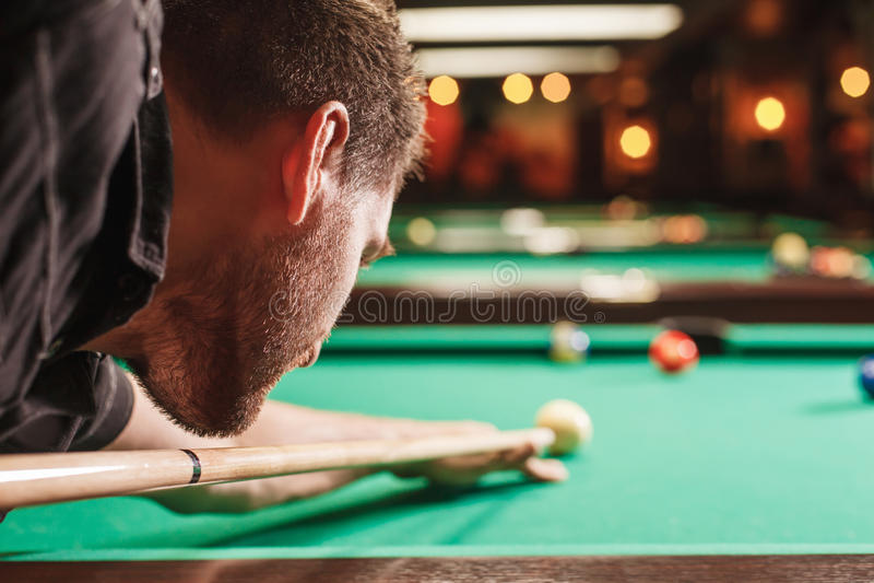 Man att försöka att slå bollen i billiard arkivfoto