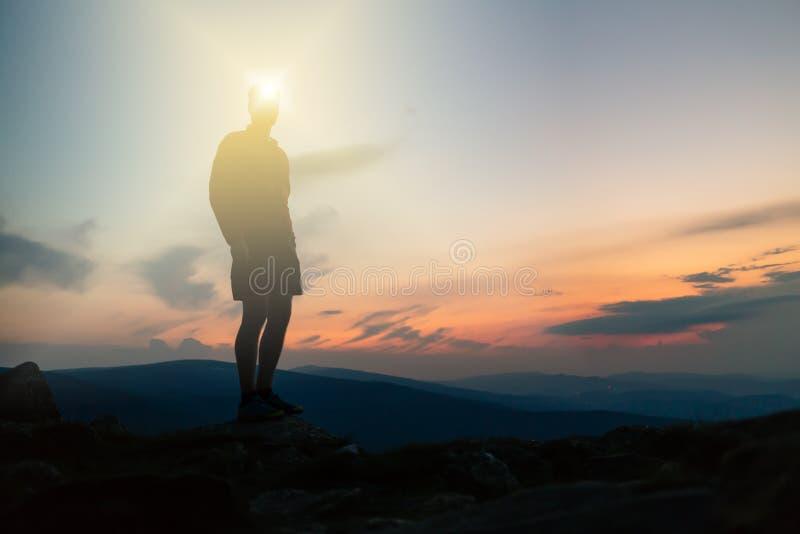 Man att fira solnedgången som ser sikt i berg royaltyfri bild