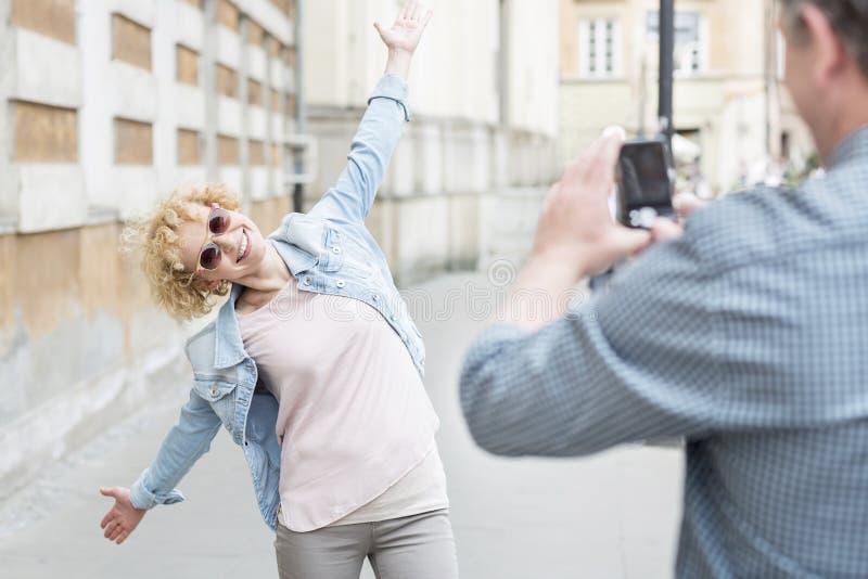 Man att fotografera skämtsamt kvinnaanseende med armar som är utsträckta på stadsgatan royaltyfri foto
