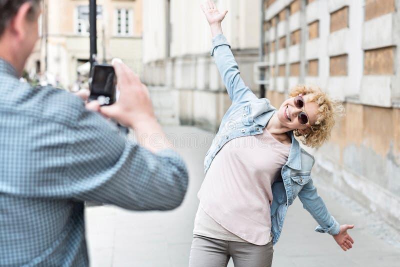Man att fotografera skämtsamt kvinnaanseende med armar som är utsträckta på stadsgatan royaltyfria bilder