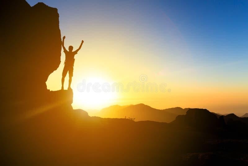 Man att fotvandra konturn i berg, havet och solnedgång arkivbild