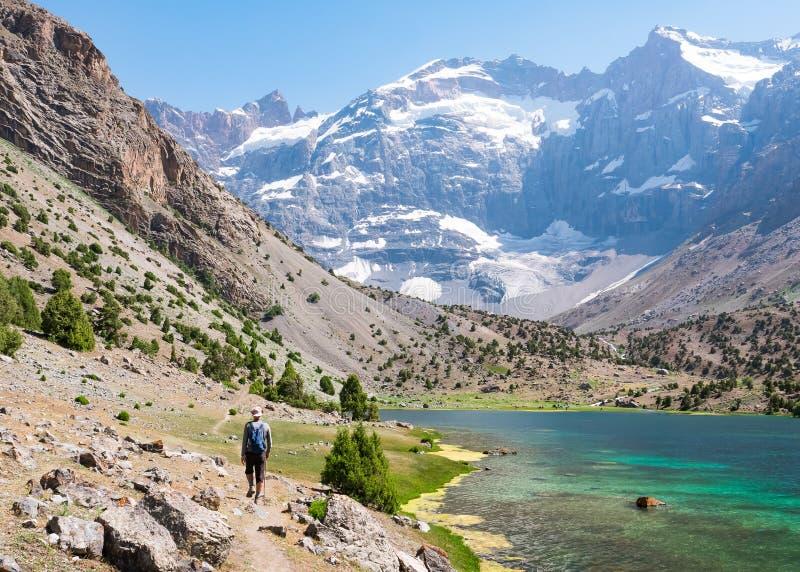 Man att fotvandra runt om Kulikalon sjöarna i Fann berg, Tajikis royaltyfria foton