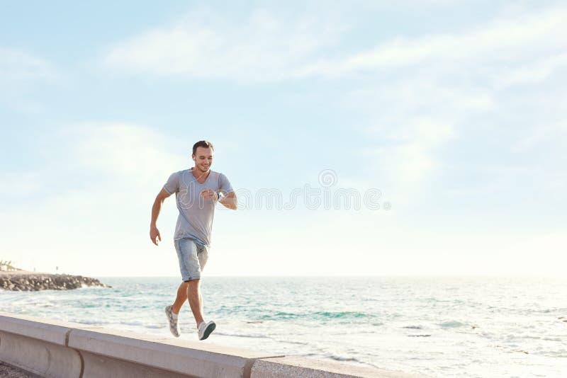 Man att gå över pir nära havet med hörlurar och musik royaltyfri bild