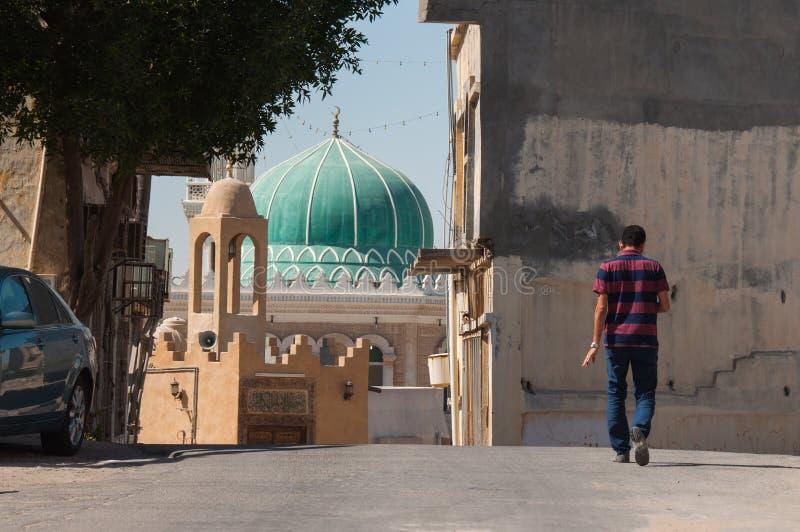 Man att gå i gator av Tarout, Saudiarabien royaltyfria bilder