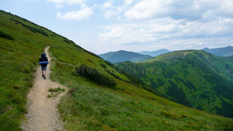 Man att gå i kullar på banan med den stora påsen i tatraberg royaltyfri foto