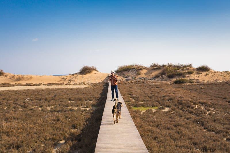 Man att gå med hans hund på en väg som leder till och med härligt landskap arkivbild