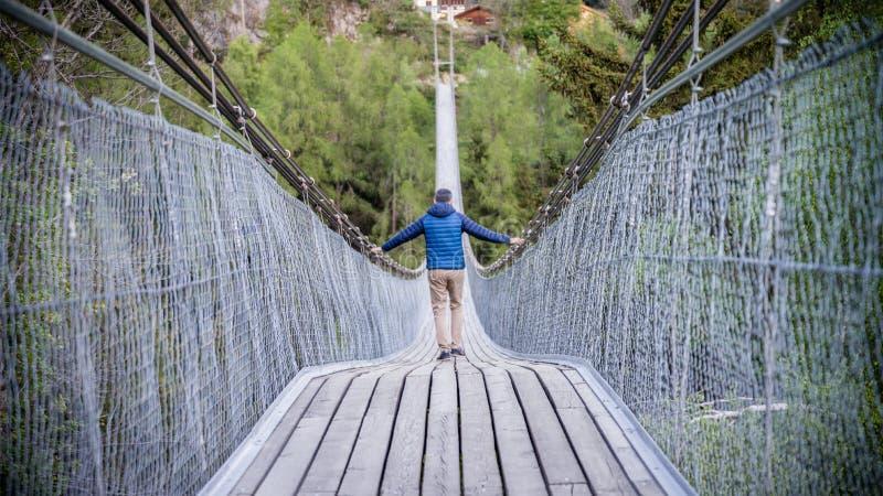 Man att gå ner på Goms den hängande bron i Schweiz arkivbilder