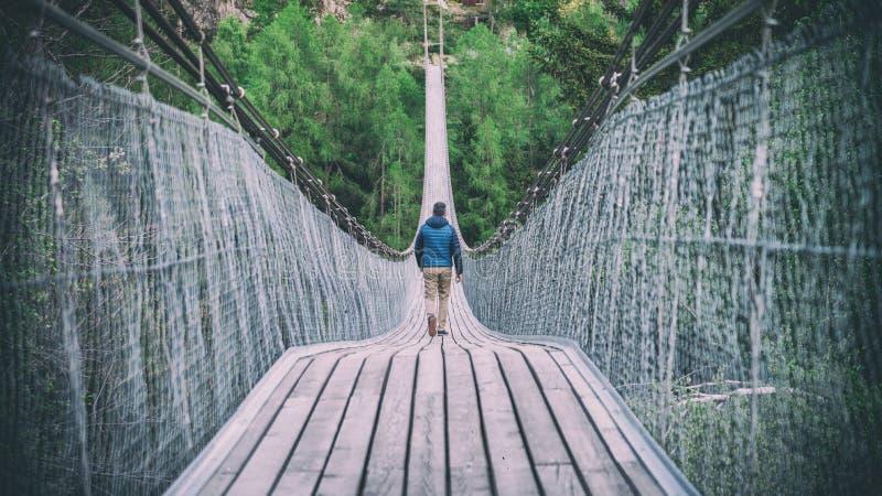 Man att gå ner på Goms den hängande bron i Schweiz royaltyfri foto