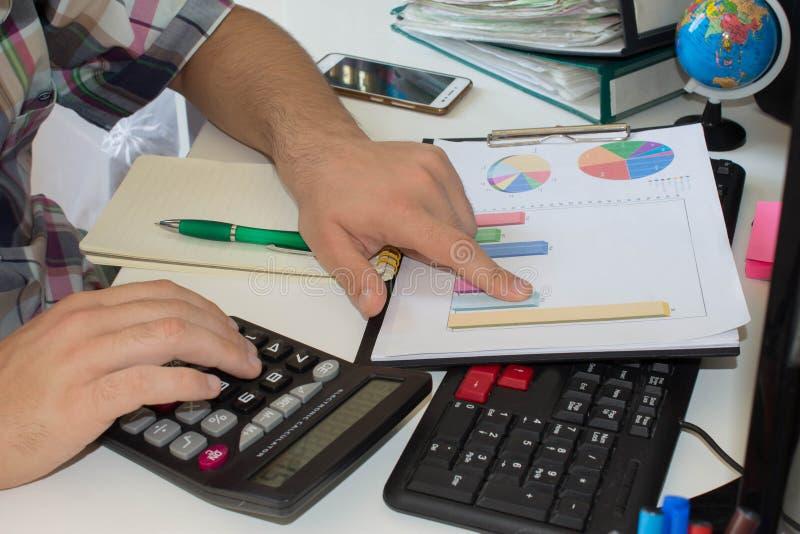 Man att göra hans redovisning, finansiellt konsulentarbete arkivbild