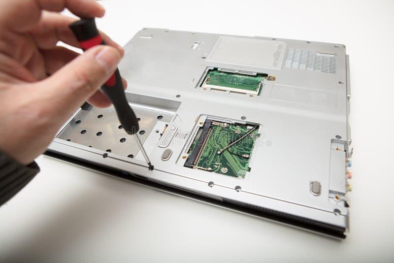 Man att göra justeringar och reparationer till en bärbar dator royaltyfri bild