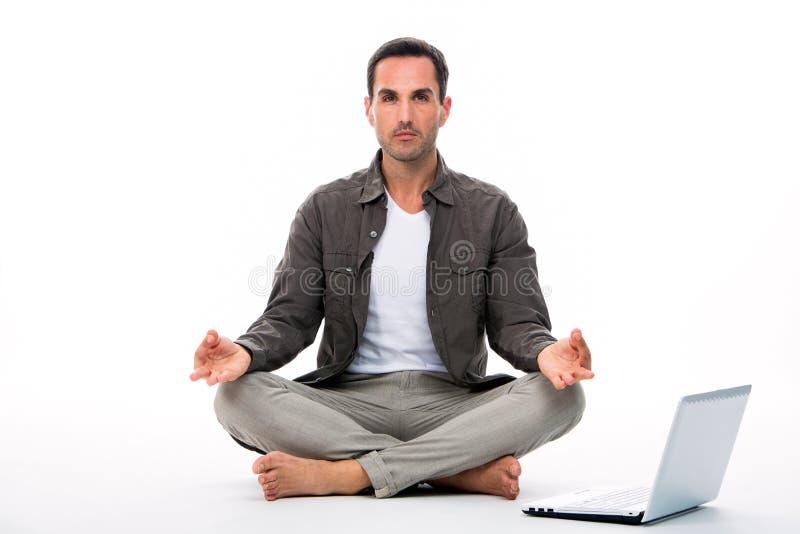 Man att göra yoga hemma med bärbara datorn bredvid honom royaltyfri bild