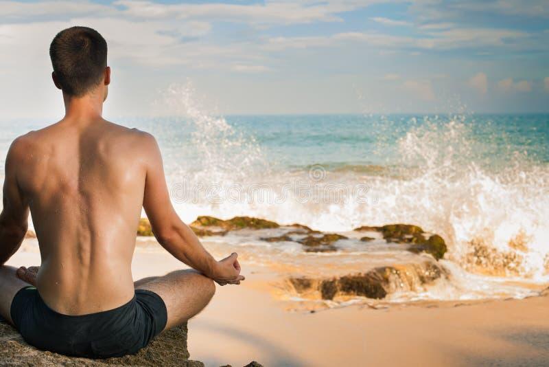 Man att göra yogameditationen, den Lotus positionen som sitter nära havsvatten royaltyfria foton