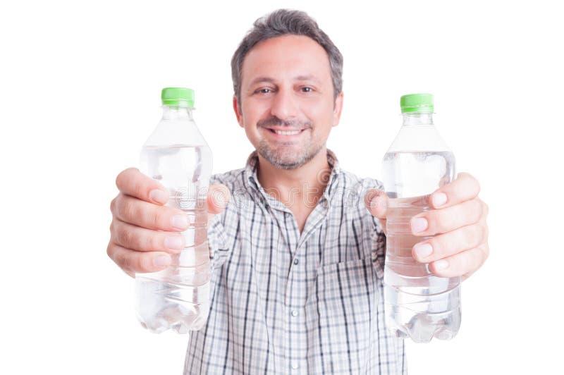 Man att ge eller att erbjuda två flaskor av kallt vatten fotografering för bildbyråer