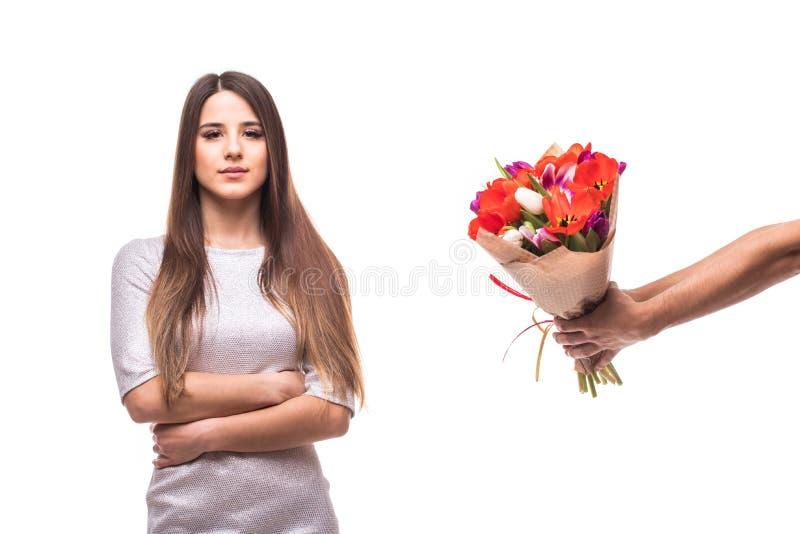 Man att ge en grupp av blommor och den ledsna kvinnan som isoleras på vit bakgrund arkivbild