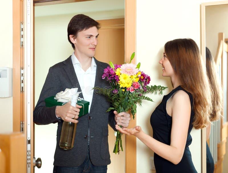 Man att ge gruppen av blommor och gåvaasken till hans unga fru royaltyfri bild