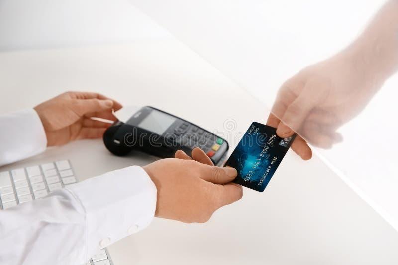Man att ge kreditkorten till kassören på fönstret för den kontanta avdelningen fotografering för bildbyråer